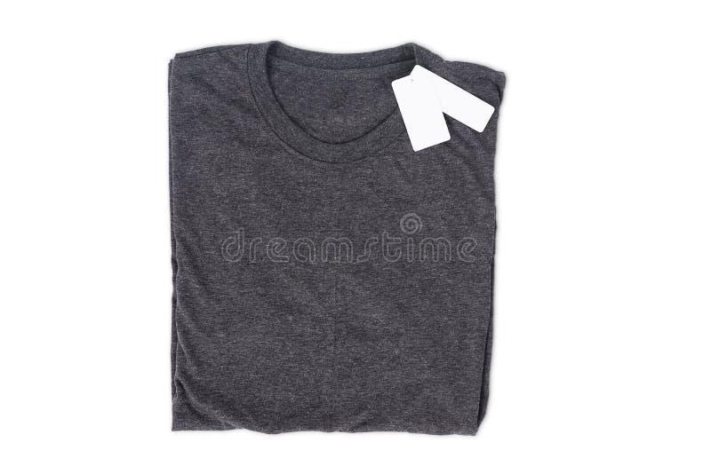 Η διπλωμένη μπλούζα με την ετικέττα απομονώνει στο άσπρο υπόβαθρο με το ψαλίδισμα της πορείας για το πρότυπο σχεδίου στοκ φωτογραφίες