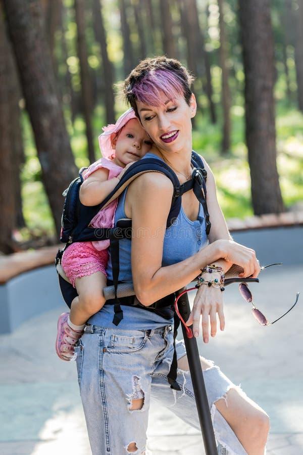 Η δροσερή ελκυστική γυναίκα απολαμβάνει ένα ηλεκτρικό μηχανικό δίκυκλο με την κόρη της στη σφεντόνα στοκ φωτογραφίες με δικαίωμα ελεύθερης χρήσης