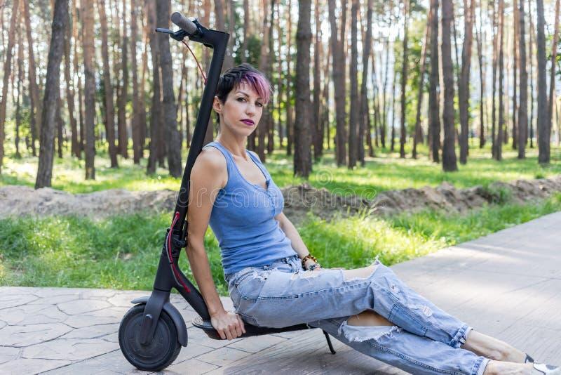 Η δροσερή ελκυστική γυναίκα με τη ρόδινη τρίχα, απολαμβάνει ένα ηλεκτρικό μηχανικό δίκυκλο στοκ φωτογραφίες