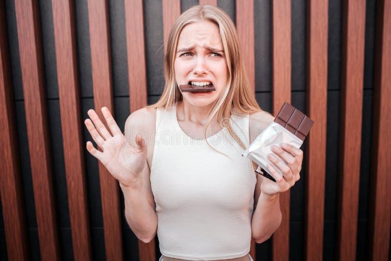 Η δυστυχισμένη νέα γυναίκα κρατά έναν φραγμό σοκολάτας διαθέσιμο και τρώει το μεγάλο κομμάτι συγχρόνως Αισθάνεται ένοχη για στοκ φωτογραφίες με δικαίωμα ελεύθερης χρήσης