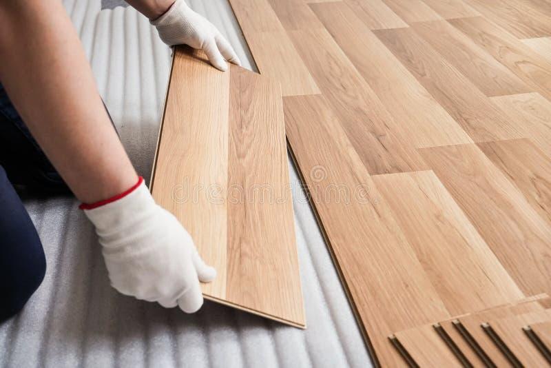 Η εγκατάσταση τοποθέτησε το πάτωμα, λεπτομέρεια σε ετοιμότητα ατόμων με τα άσπρα γάντια που εγκαθιστούν σε στρώματα το ξύλινο κερ στοκ εικόνα