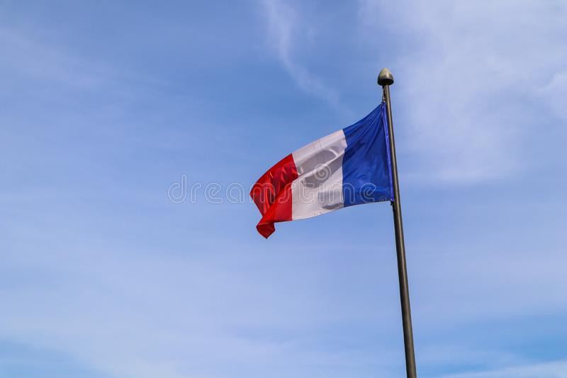 Η εθνική σημαία της Γαλλίας στο κοντάρι σημαίας αναπτύσσεται στον αέρα ενάντια στο μπλε ουρανό στοκ εικόνες με δικαίωμα ελεύθερης χρήσης