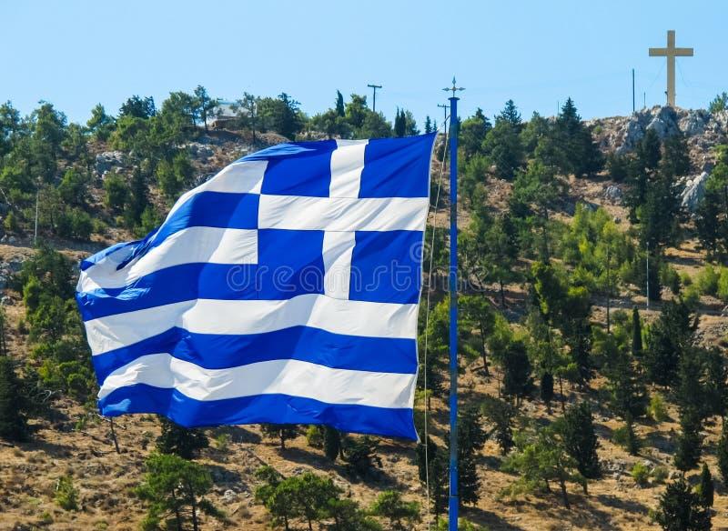 Η εθνική σημαία της Ελλάδας στο κοντάρι σημαίας αναπτύσσεται στον αέρα στα πλαίσια ενός λόφου με τα πράσινα δέντρα και έναν σταυρ στοκ εικόνα