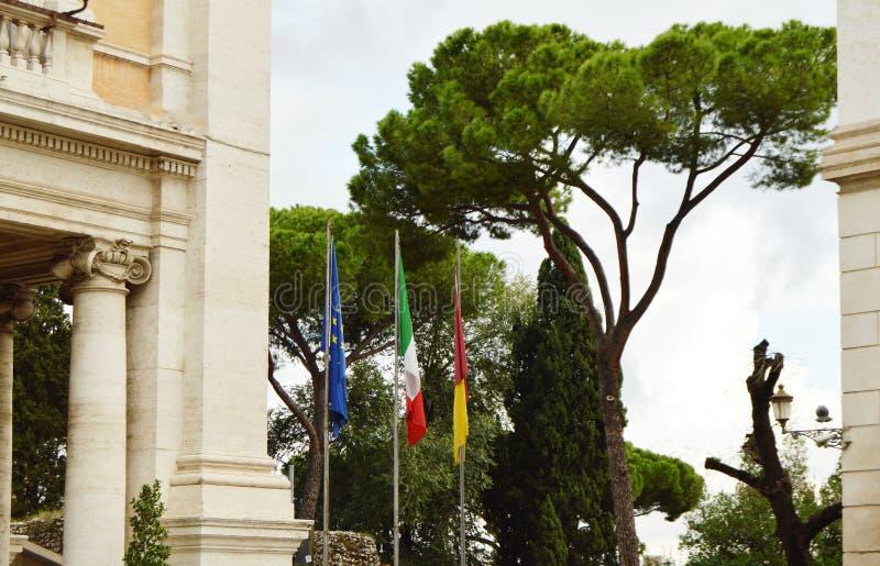 Η εθνική σημαία της Ιταλίας, η σημαία της ΕΕ της Ευρωπαϊκής Ένωσης της πόλης της Ρώμης στο κοντάρι σημαίας κοντά στην αίθουσα πόλ στοκ εικόνες