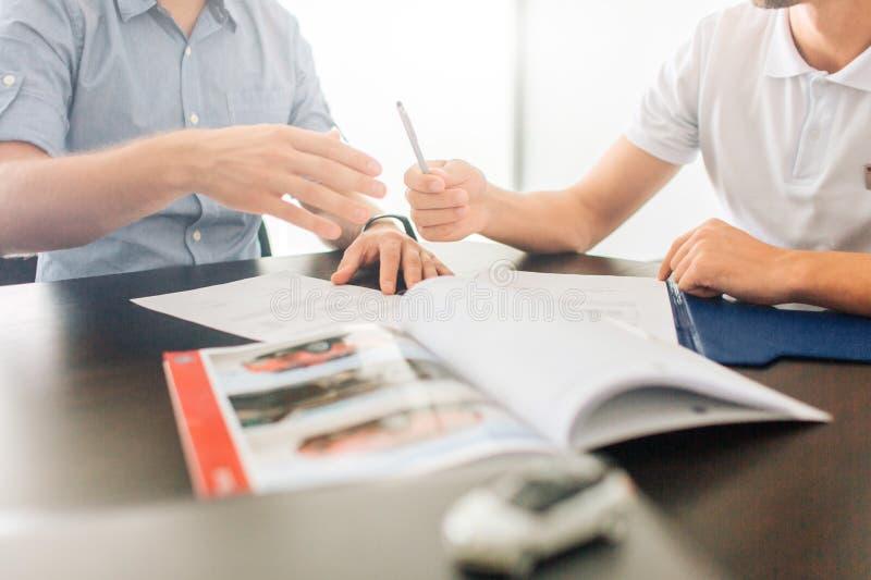 Η εικόνα δύο ατόμων κάθεται στον πίνακα από κοινού Κρατούν τα χέρια στα έγγραφα Ο τύπος στο δικαίωμα δίνει τη μάνδρα στο άτομο στ στοκ εικόνα