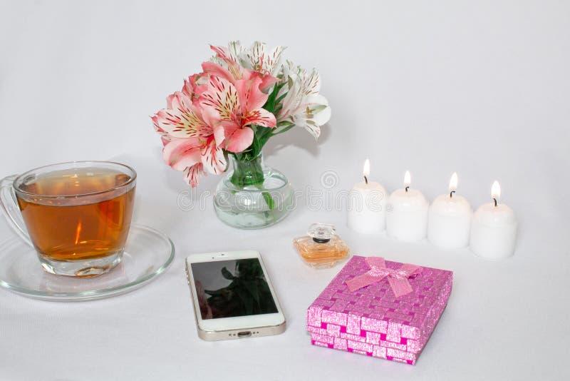 Η εικόνα ενός ρόδινου κιβωτίου δώρων πολυτέλειας με μια ανθοδέσμη όμορφου Alstroemeria ανθίζει, ρομαντικά κεριά, αρωματοποιία, φλ στοκ εικόνες με δικαίωμα ελεύθερης χρήσης
