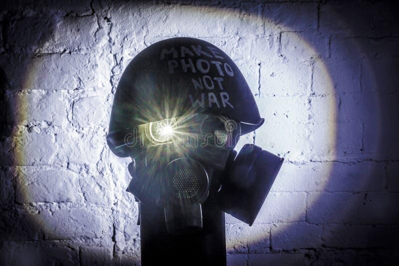 Η εικόνα τέχνης μιας στρατιωτικής μάσκας αερίου σε έναν άσπρο τουβλότοιχο με τις σκιές με τη λάμψη με την επιγραφή κάνει τον πόλε στοκ φωτογραφία