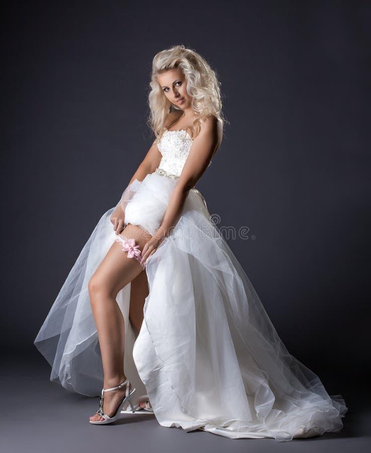 Η εικόνα της αισθησιακής νέας νύφης παρουσιάζει garter στο πόδι στοκ εικόνες