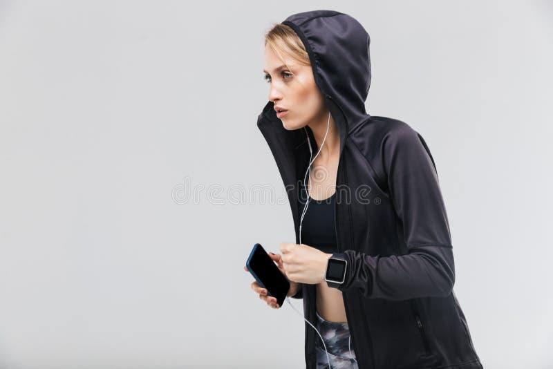 Η εικόνα της ενεργού ξανθής δεκαετίας του '20 γυναικών έντυσε sportswear ακούοντας τη μουσική με τα ακουστικά τρέχοντας στοκ φωτογραφίες
