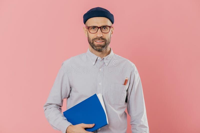 Η εικόνα του γεμάτου αυτοπεποίθηση νέου αρσενικού με τις καλαμιές, φορά τα διαφανή γυαλιά, κρατά το εγχειρίδιο κάτω από το σκέλος στοκ φωτογραφία με δικαίωμα ελεύθερης χρήσης