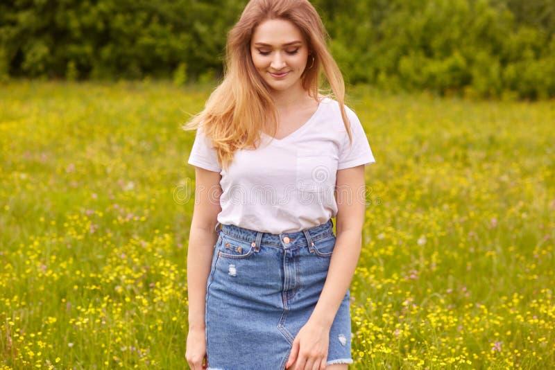 Η εικόνα του νέου όμορφου καυκάσιου κοριτσιού στην άσπρη μπλούζα και την μπλε φούστα τζιν, που θέτει στο λιβάδι και που κοιτάζει  στοκ εικόνα