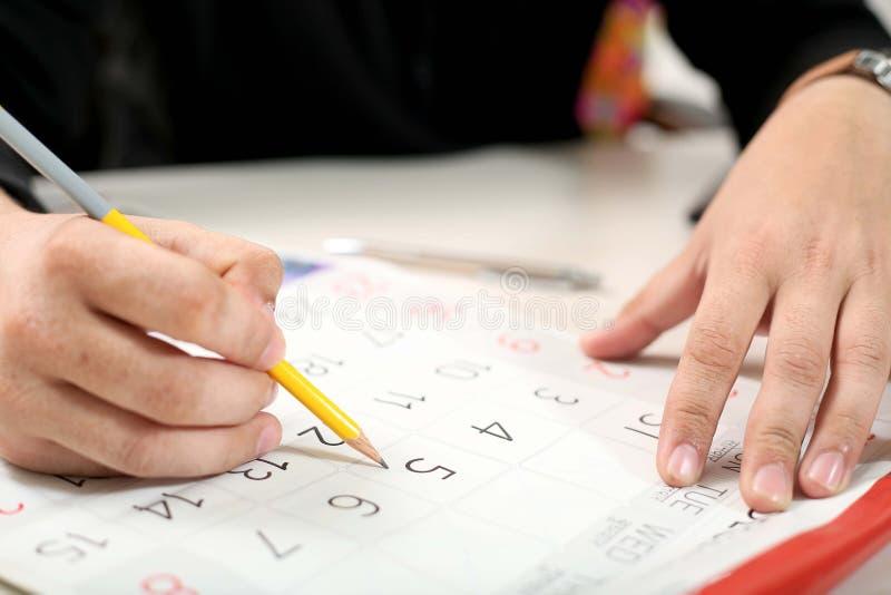 Η εικόνα του χεριού κρατά το μολύβι διαθέσιμο με το ημερολόγιο στοκ φωτογραφία με δικαίωμα ελεύθερης χρήσης