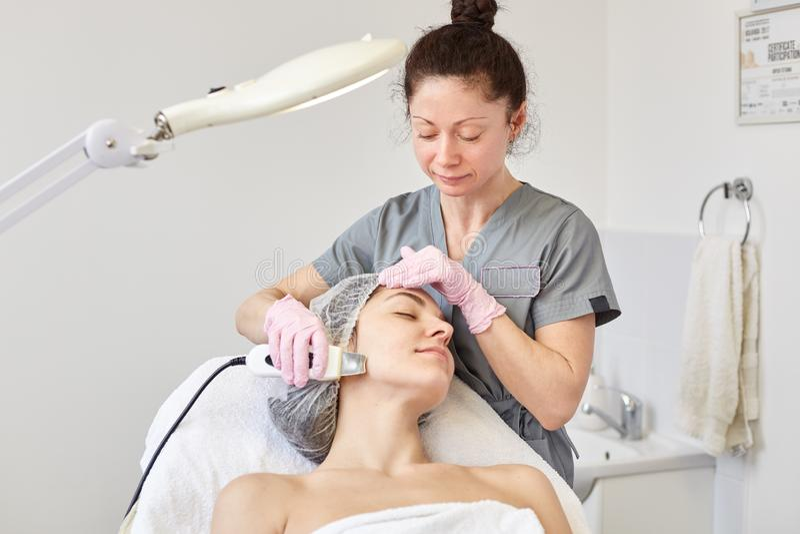Η εικόνα του cosmetologist brunette φορά τα γκρίζα ενδύματα που κάνουν τις εξαιρετικά ηχιτικές διαδικασίες για τη νέα κυρία που β στοκ εικόνες