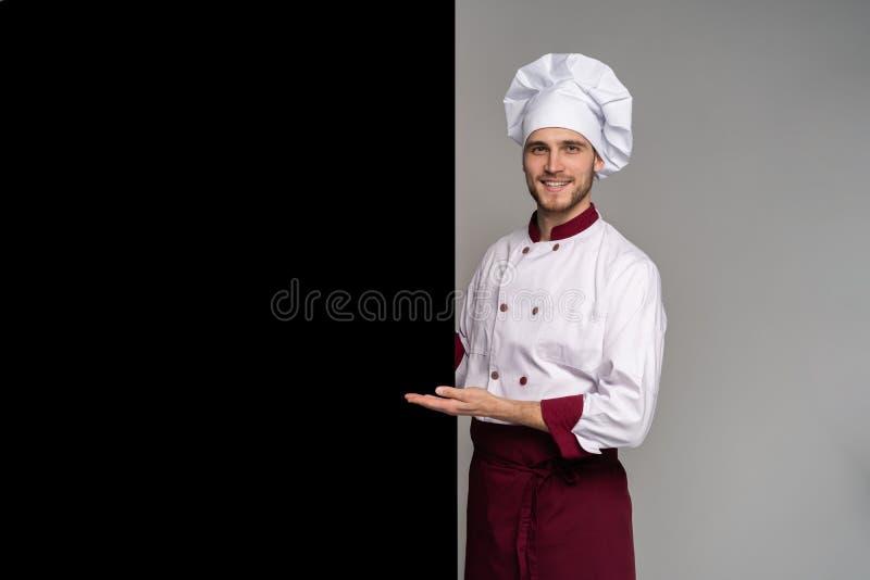 Η εικόνα των χαμογελώντας νεολαιών μαγειρεύει στην ομοιόμορφη στάση που απομονώνεται πέρα από το γκρίζο υπόβαθρο τοίχων Υπόδειξη  στοκ φωτογραφία με δικαίωμα ελεύθερης χρήσης