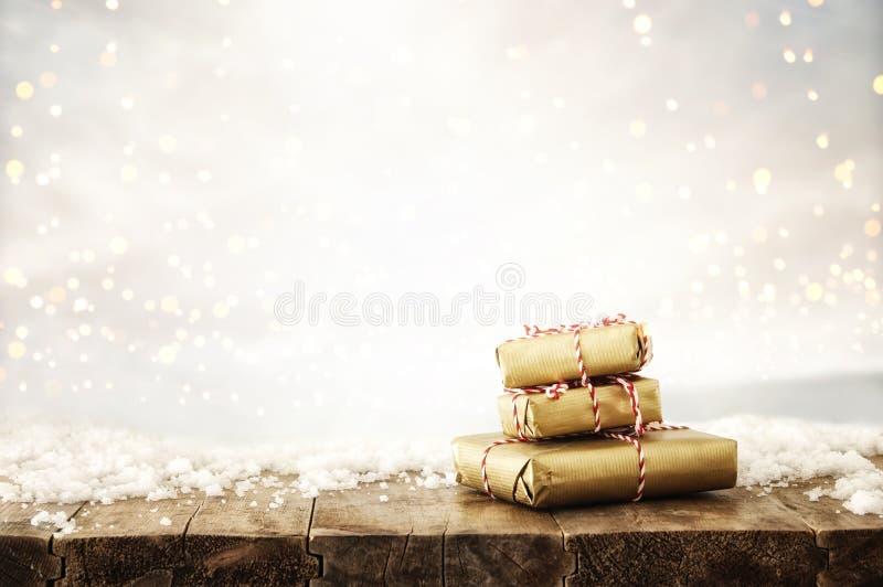 η εικόνα των χειροποίητων τυλιγμένων κιβωτίων δώρων πέρα από τον ξύλινο πίνακα που καλύπτεται με το χιόνι και το ασήμι ακτινοβολο στοκ φωτογραφίες με δικαίωμα ελεύθερης χρήσης