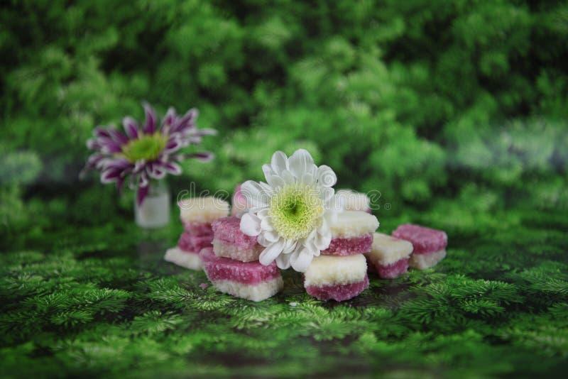 Η εικόνα φωτογραφίας τροφίμων Χριστουγέννων με τον ντεμοντέ αγγλικό πάγο καρύδων μεταχειρίζεται με τα χειμερινά λουλούδια στο υπό στοκ φωτογραφία με δικαίωμα ελεύθερης χρήσης