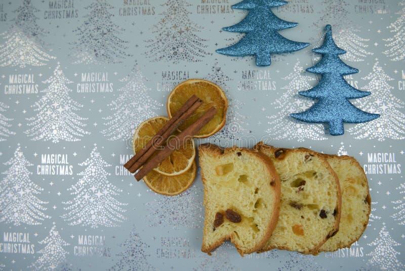 Η εικόνα φωτογραφίας τροφίμων Χριστουγέννων με το εποχιακό ιταλικό πορτοκάλι κέικ panettone και η κανέλα με ακτινοβολούν μπλε υπό στοκ φωτογραφία με δικαίωμα ελεύθερης χρήσης
