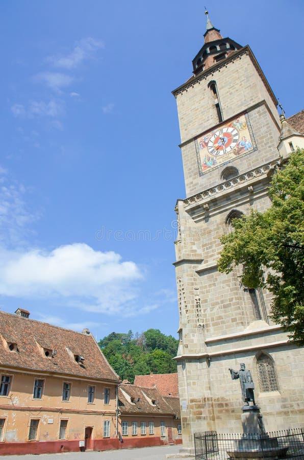 Η εκκλησία Biserica Neagra (η μαύρη εκκλησία) που τοποθετείται κοντά στο τετραγωνικό Piata Sfatului, και το άγαλμα του Johannes H στοκ φωτογραφία με δικαίωμα ελεύθερης χρήσης