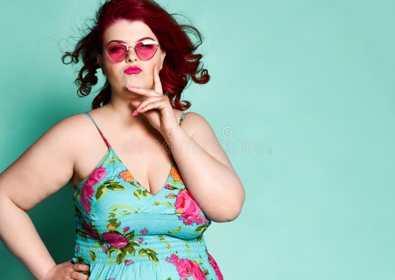 Η εκλεκτική γυναικεία υπέρβαρη γυναίκα συν-μεγέθους στα σύγχρονα γυαλιά ηλίου και τα ζωηρόχρωμα sundress με το χέρι της στο μάγου στοκ εικόνες