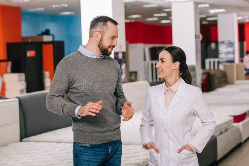 η εκλεκτική εστίαση του αρσενικού πελάτη και ο βοηθός καταστημάτων στο άσπρο παλτό στα έπιπλα ψωνίζουν με τακτοποιημένος στοκ εικόνες με δικαίωμα ελεύθερης χρήσης