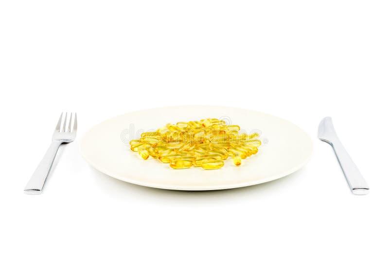 Η εκλεκτική εστίαση των μαλακών κίτρινων καψών με υγιή ωμέγα 3 αλιεύει το πετρέλαιο σε ένα πιάτο γευμάτων με το μαχαίρι και το δί στοκ εικόνα με δικαίωμα ελεύθερης χρήσης