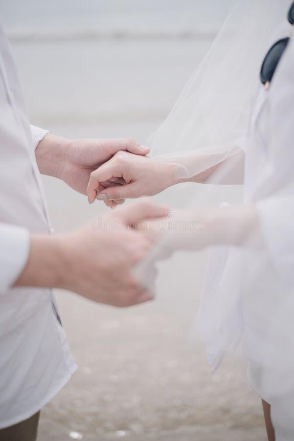 Η εκμετάλλευση γαμήλιων ζευγών μεταξύ τους χέρι με το υπόβαθρο παραλιών, έννοια αγάπης στοκ φωτογραφία