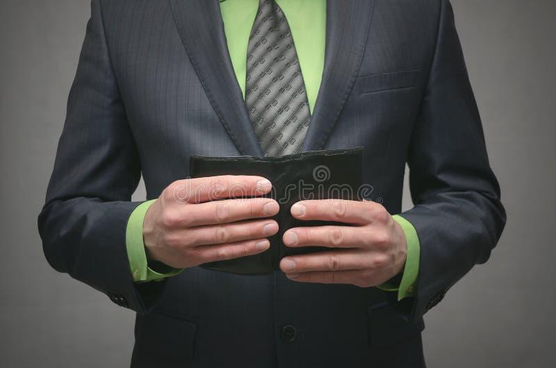 Η εκμετάλλευση επιχειρηματιών στα χέρια ένα μαύρο πορτοφόλι δέρματος, κλείνει επάνω τη φωτογραφία στοκ φωτογραφία με δικαίωμα ελεύθερης χρήσης