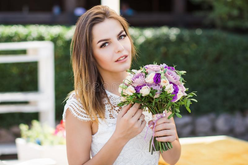 Η εκμετάλλευση κοριτσιών ανθίζει στα χέρια, νέα όμορφη νύφη στην άσπρη γαμήλια ανθοδέσμη εκμετάλλευσης φορεμάτων, ανθοδέσμη της ν στοκ φωτογραφίες