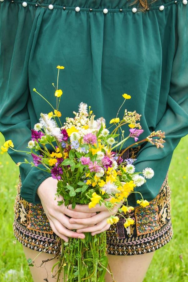 Η εκμετάλλευση κοριτσιών σε την δίνει μια όμορφη ανθοδέσμη με τα πολύχρωμα άγρια λουλούδια Καταπληκτική δέσμη των λουλουδιών wilf στοκ εικόνα