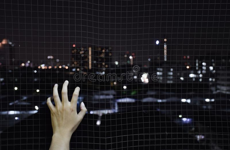 Η εκμετάλλευση χεριών στο καθαρό κλουβί σιδήρου θέλει να πάει το υπόβαθρο πόλεων στοκ εικόνες