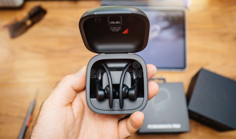 Η εκμετάλλευση Powerbeats χεριών ατόμων υπέρ κτυπά τα ακουστικά στοκ φωτογραφία με δικαίωμα ελεύθερης χρήσης