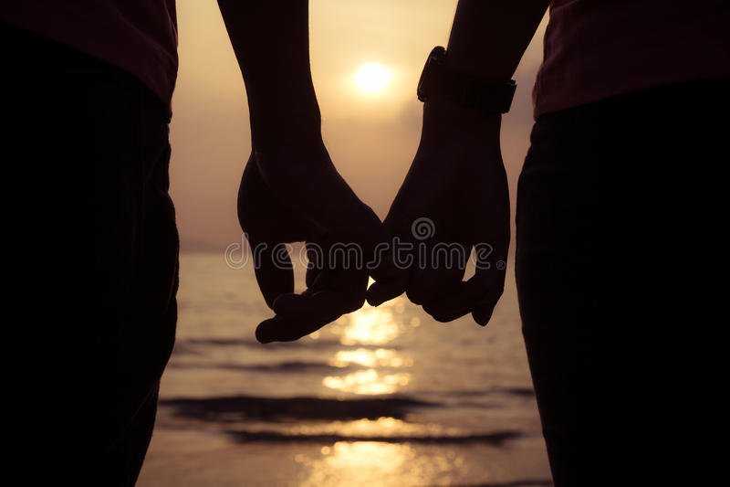 η εκμετάλλευση ζευγών αγάπης δίνει τα δάχτυλα στο ηλιοβασίλεμα στην παραλία στοκ εικόνα