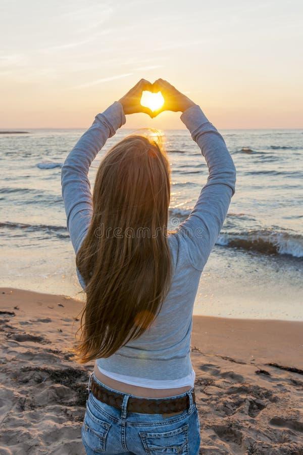 Η εκμετάλλευση κοριτσιών παραδίδει τη μορφή καρδιών στην παραλία στοκ φωτογραφία με δικαίωμα ελεύθερης χρήσης