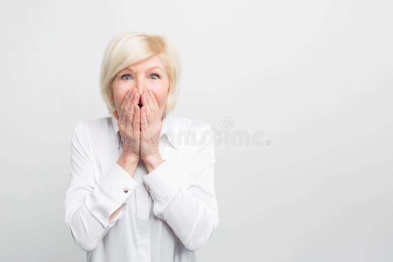 Η εκπληκτικά όμορφη και πανέμορφη ηλικιωμένη γυναίκα κρατά το χέρι της στο στόμα, που δείχνει ότι είναι πολύ έκπληκτη στοκ φωτογραφία