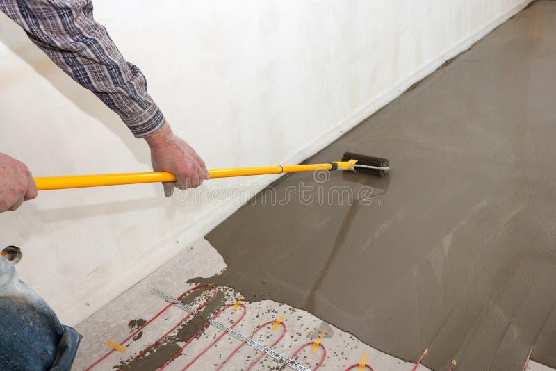 Ηλεκτρική εγκατάσταση συστημάτων θέρμανσης πατωμάτων στο καινούργιο σπίτι Ο εργαζόμενος ευθυγραμμίζει το τσιμέντο με τον κύλινδρο στοκ εικόνα με δικαίωμα ελεύθερης χρήσης