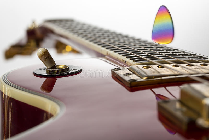 Ηλεκτρική κιθάρα με την πετώντας επιλογή ουράνιων τόξων στοκ φωτογραφία