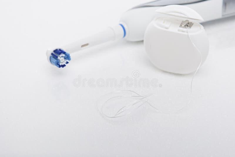 Ηλεκτρική οδοντόβουρτσα και οδοντικό νήμα στο λευκό στοκ φωτογραφίες
