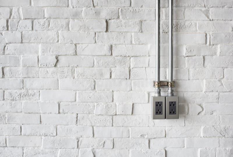 Ηλεκτρική υποδοχή σε έναν άσπρο χρωματισμένο τουβλότοιχο στοκ εικόνα