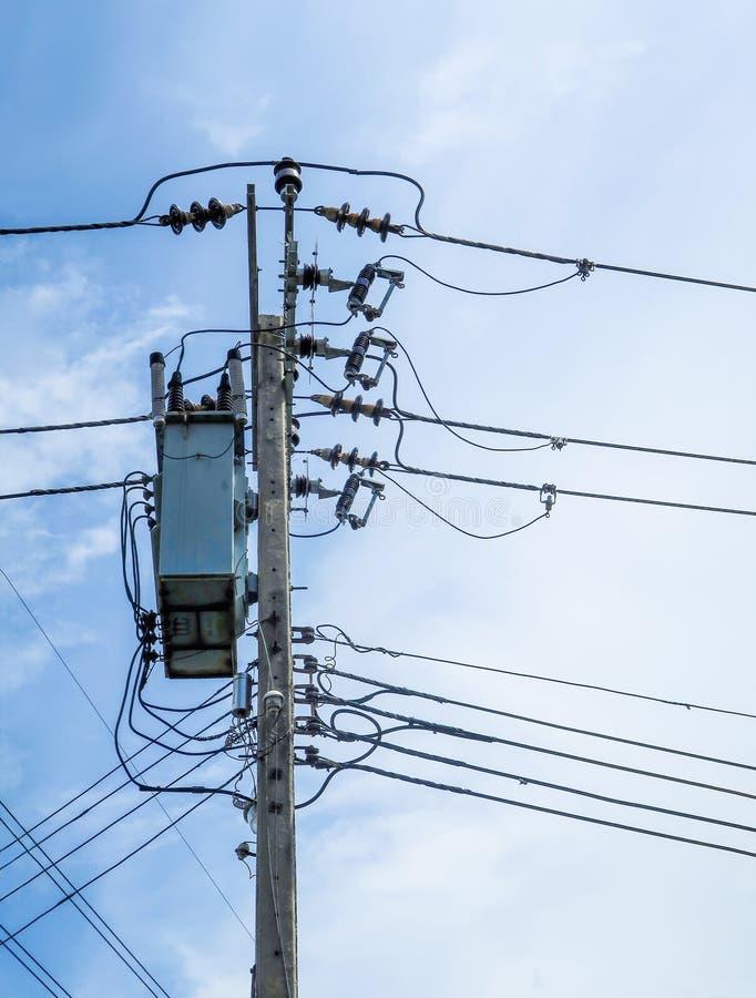 Ηλεκτρικοί πόλος και καλώδιο στο μπλε ουρανό στοκ εικόνα
