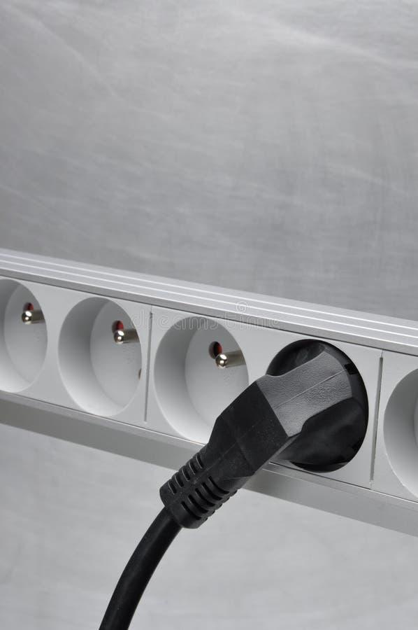 Ηλεκτρικό σκοινί με τη λουρίδα δύναμης στο γκρίζο υπόβαθρο μετάλλων στοκ φωτογραφία με δικαίωμα ελεύθερης χρήσης