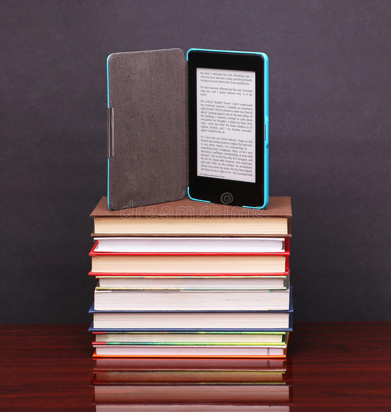 Ηλεκτρονικά παλαιά βιβλία αναγνωστών και σωρών βιβλίων στο ξύλινο γραφείο στοκ εικόνα