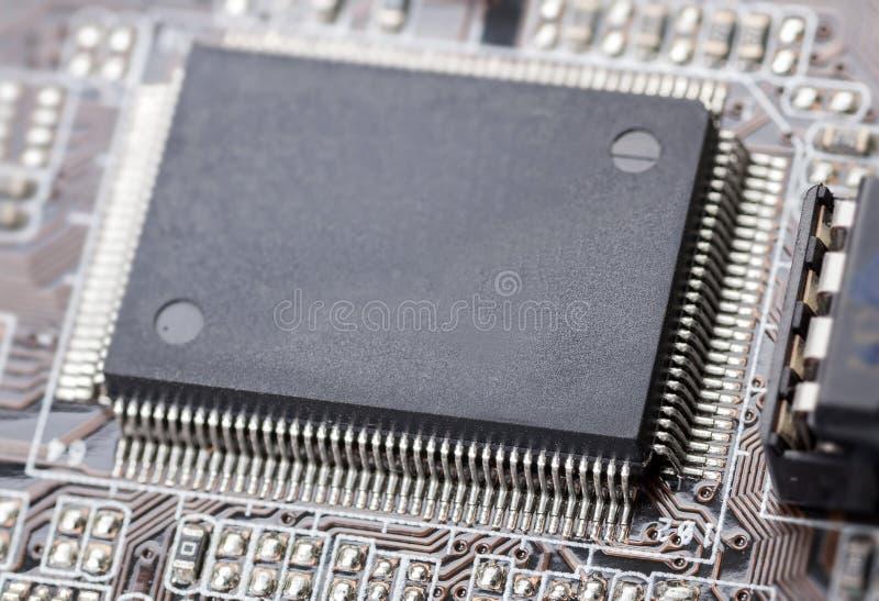Ηλεκτρονικό τσιπ στο χαρτόνι κυκλωμάτων υπολογιστών στοκ εικόνα