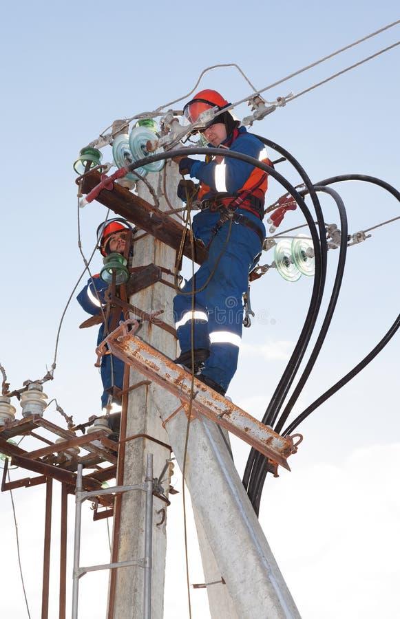 Ηλεκτρολόγοι στις μπλε φόρμες που λειτουργούν στο ύψος στοκ εικόνα