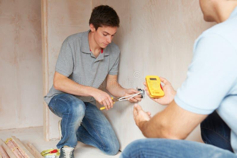 Ηλεκτρολόγος με την εργασία μαθητευόμενων στο νέο σπίτι στοκ εικόνα με δικαίωμα ελεύθερης χρήσης