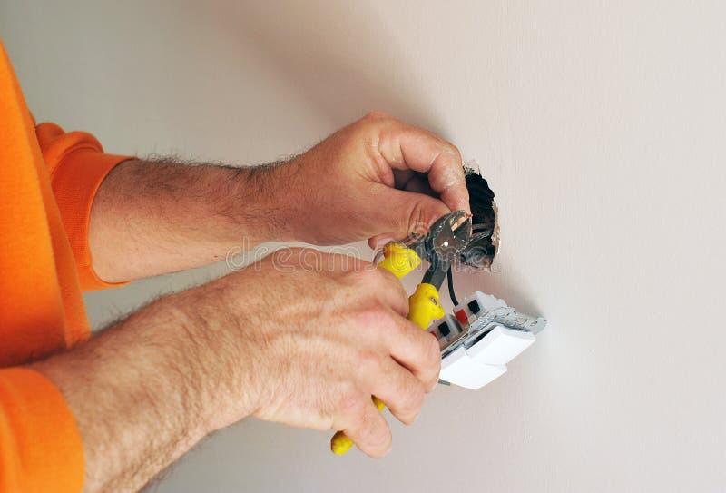 Ηλεκτρολόγος που εγκαθιστά τους ηλεκτρικούς διακόπτες στο καινούργιο σπίτι στοκ εικόνες