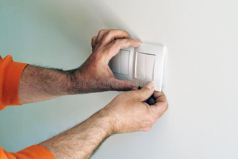 Ηλεκτρολόγος που εγκαθιστά τους ηλεκτρικούς διακόπτες στο καινούργιο σπίτι στοκ φωτογραφίες
