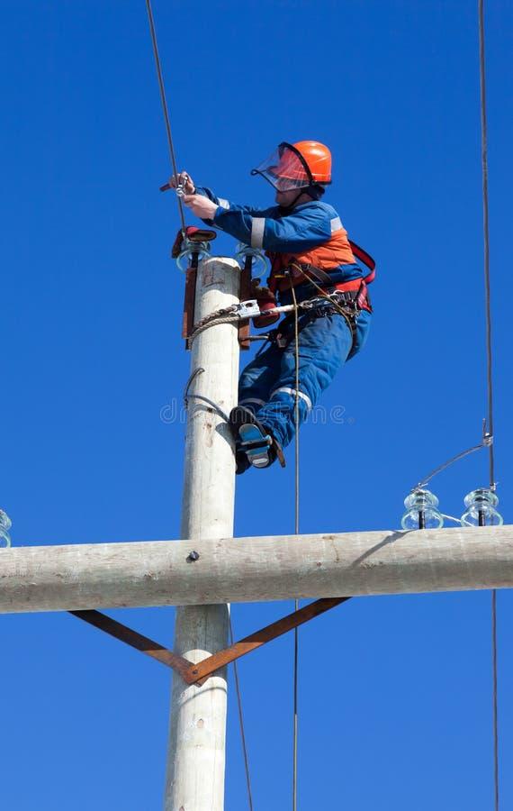 Ηλεκτρολόγος που εργάζεται πάνω από έναν πυλώνα ηλεκτρικής ενέργειας στοκ φωτογραφία