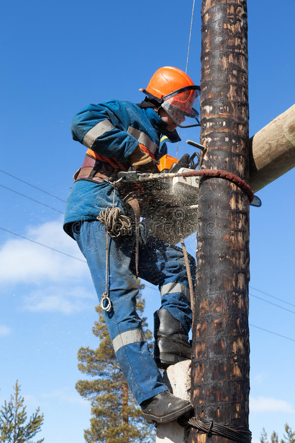 Ηλεκτρολόγος που εργάζεται στο pylon αλυσιδοπρίονο ηλεκτρικής ενέργειας στοκ φωτογραφία