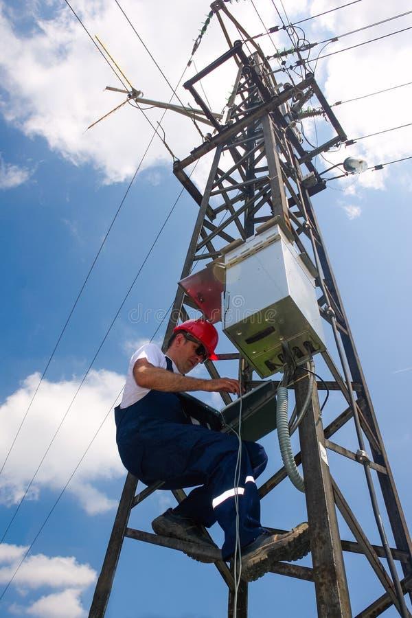 Ηλεκτρολόγος στο κόκκινο κράνος που λειτουργεί στον πόλο ηλεκτρικής δύναμης στοκ εικόνες