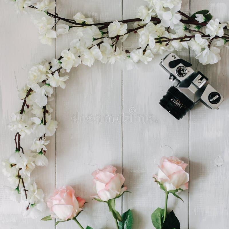 Η εκλεκτής ποιότητας κάμερα ταινιών, κλάδος sakura, ρόδινος αυξήθηκε λουλούδια στο άσπρο ξύλινο γραφείο Η τοπ άποψη, επίπεδη βάζε στοκ φωτογραφία